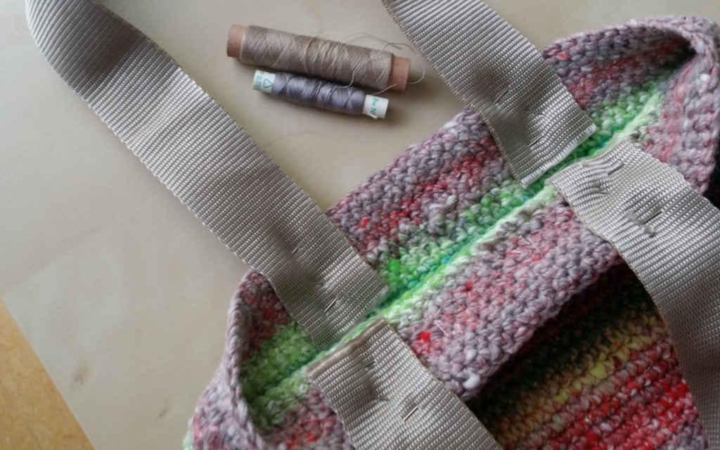 Annähen der Ripsbänder als Henkel für die Tasche aus Noro Kagayaki 17 und Noro Tayio 31. Foto: Katrin Walter – Noromaniac