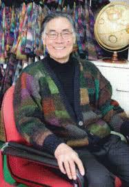 Eisaku Noro mit einer Strickjacke aus seinem Garn, sitzend, lächelnd. (Vermutlich trägt er Silk Garden mit Silk Garden Solo)