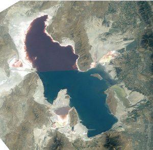Ein Salzsee von oben, halb verändert in rot-violetter Farbe durch Mikroben.
