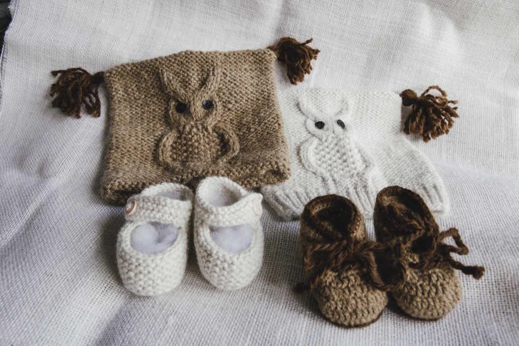 Produkte aus Alpaka-Wolle gestrickt und gehäkelt. Man sieht Mützen mit Eulenmotiv und Baby-Schuhe. Foto: Silpaca für Noromaniac