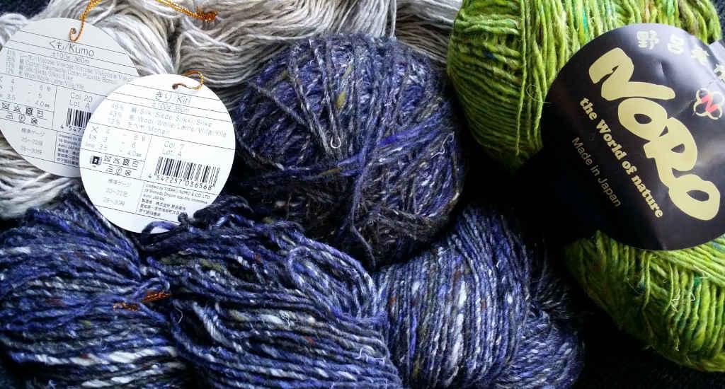 Die Noro-Garne Kiri #07 und Kumo #20 mit ihren beschreibenden Etiketten sowie mit Noro Silk Garden Sock Solo #33. Foto: Katrin Walter - Noromaniac