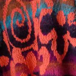 Die kleine Noro Kureyon als gestrickte Weste. Detail aus dem orange-farbenen Blumen-Intarsien-Muster. Foto: Katrin Walter - Noromaniac