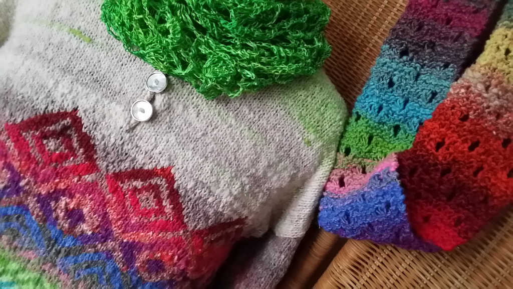 Nahaufnahme des grünen Seidentuches aus Dibadue-Funnies, dem Loop aus Noro Taiyo 31 und dem Pullover aus Noro Kagayaki 17. Foto: Katrin Walter – Noromaniac