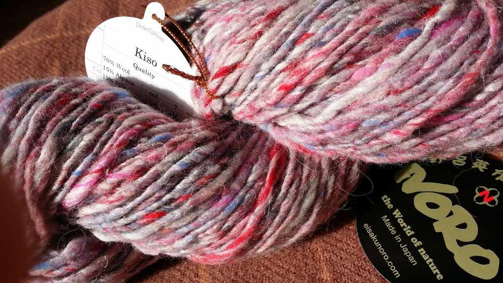 Noro Kiso aus 70% Wolle, 15% Alpaka und 15% Seide, hier in Farbe 07 mit Rosa, Hellblau und Weiß
