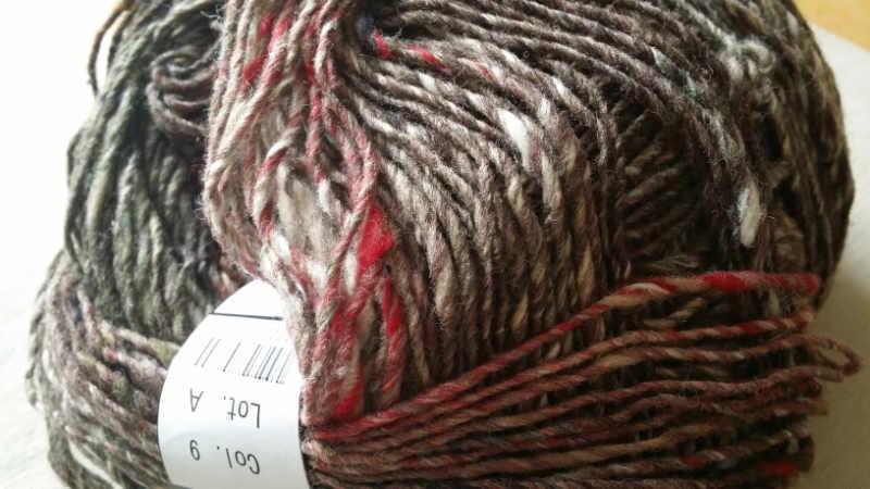 Ein Garn-Knäuel Noto Kotori der Farbe #09 mit Brauntönen und Highlights in Natur und Weinrot. Foto: Katrin Walter - Noromaniac