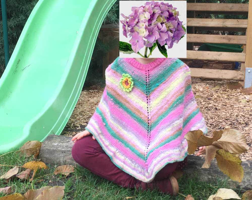 Susaki im rosa Ponchoglück. Mädchen mit Cape aus Norowolle-Farbverlaufsgarn sitzend im Gra. sFoto: Katrin Walter – Noromaniac