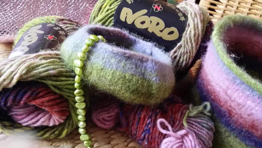 Die Wolle im Knäuel und gestrickte und gefilzte Schälchen aus der Noro Kureyon Farbe #221 mit Grün, Rosa, Flieder, Lila und Rostrot. Foto: Katrin Walter - Noromaniac