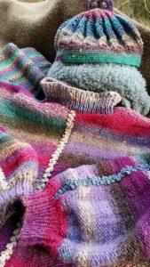 Der Pullover aus der Wolle Noro Kureyon 349 mit Ziernähten in hellbeige und Blau, passendem hellblauen Loop aus Micio und Mütze aus Shiro. Foto: Katrin Walter – Noromaniac