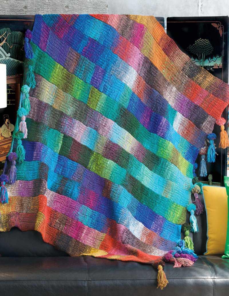 Bunte Decke mit Pompons und Trotteln, designt von Alexandra Davidoff. Sie besteht gleich aus sieben verschiedenen Farbrapporten der Norowolle - Noromaniac