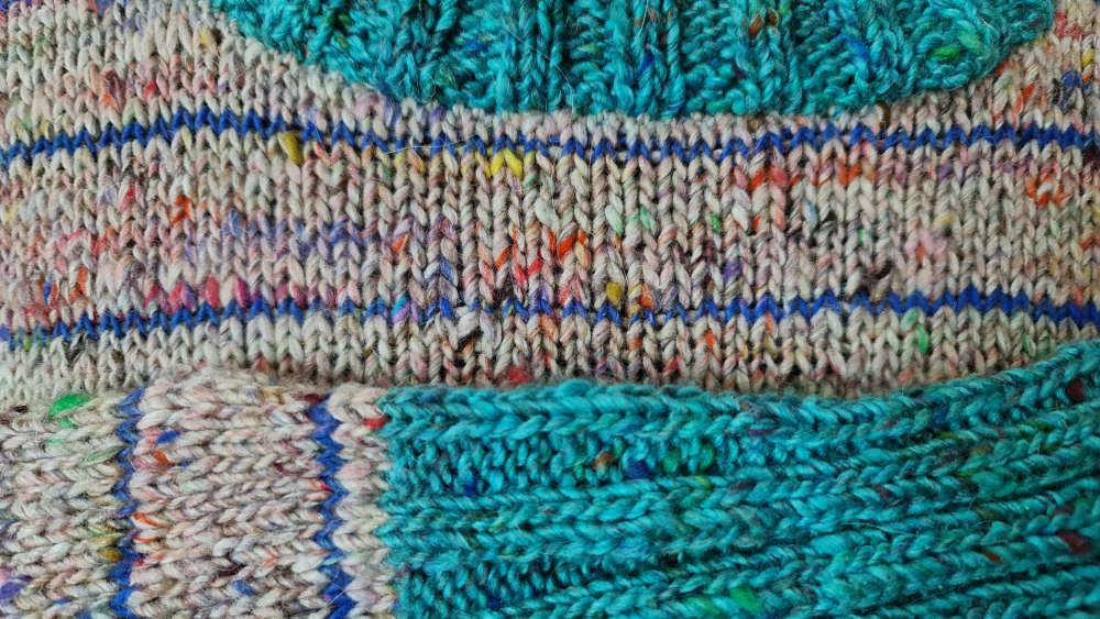 Detail aus dem Pullover von Noromaniac aus der Noro Madara Farbe #01 Sake (Neutrals) und Noro Madara #06 Kigishi (Knall-Türkis) mit dünnen blauen Streifen aus der Noro Silk Garden Sock Solo Tweed in Royalblau. Foto: Katrin Walter