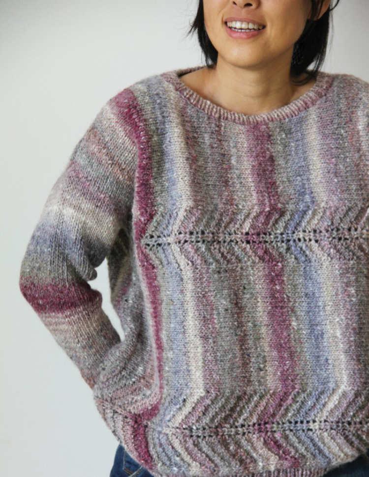 """""""Sideways Knit Pullover"""" vom Noro Design Team, wie der Name schon sagt, ein quer gestrickter Pullover aus Noro Okunoshima Farbe #02 in Natur, Bordeaux und Flieder. Foto: Noro Knitting Magazine / Knittingfever – Garn-Beschreibung Noromaniac"""