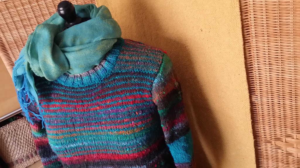 Draufsicht von oben des Pullovers aus Noro Ito 3 von Noromaniac mit türkisfarbenem Tuch. Foto: Katrin Walter