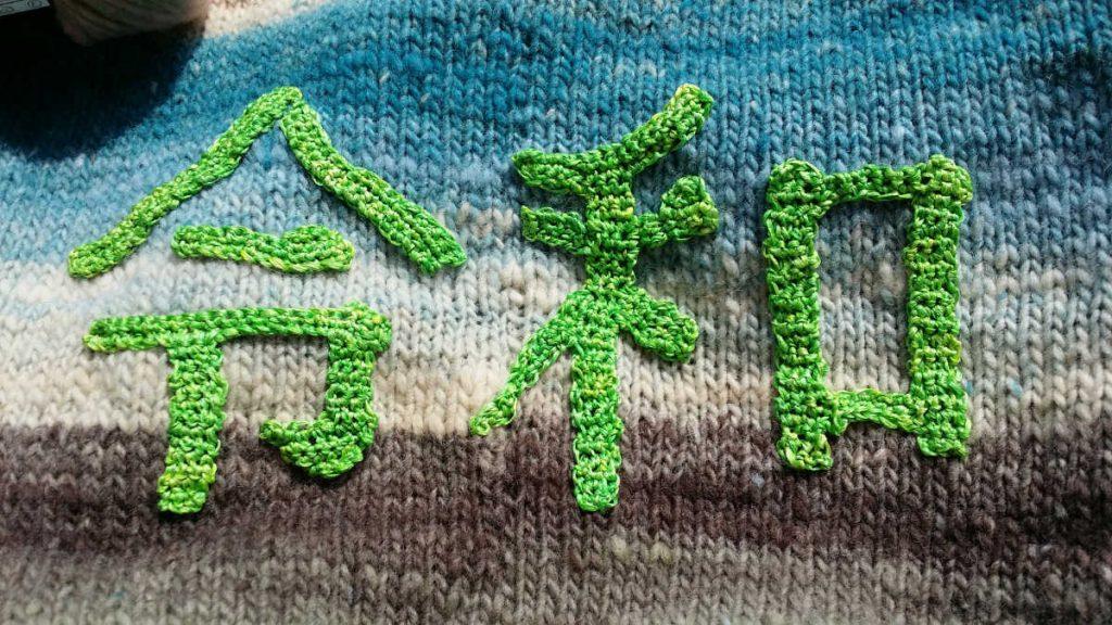 Die japanischen Schriftzeichen für Reiwa gehäkelt und aufgenäht auf dem Rückenteil des gestrickten Pullover.