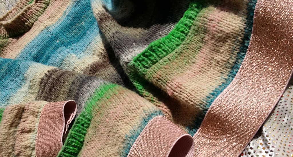 Die Bündchen aus rosefarbenem Gummiband aus der Nähe sowie die gestrickten Tascheneingriffe in grün am Reiwa-Pullover aus Noro Kureyon 343 von Noromaniac. Foto: Katrin Walter