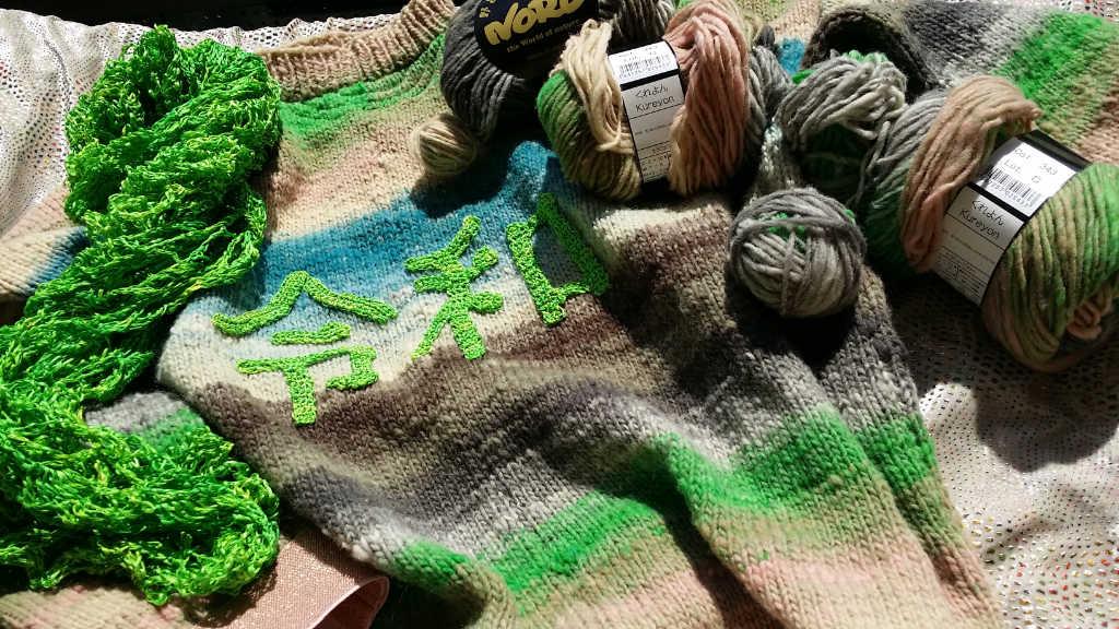 Das grüne Seidengarn im Tuch und als Reiwa-Zeichen auf dem Pullover aus Noro Kureyon von Noromaniac. Foto: Katrin Walter