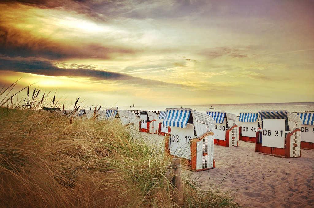 Strandkörbe am Meer mit stimmungsvollem Himmel in gelbliches Licht getaucht. Illustration zum Beitrag Weste/Top aus Norogarn Taiyo Sport 6 von Noromaniac. Foto: Pixabay