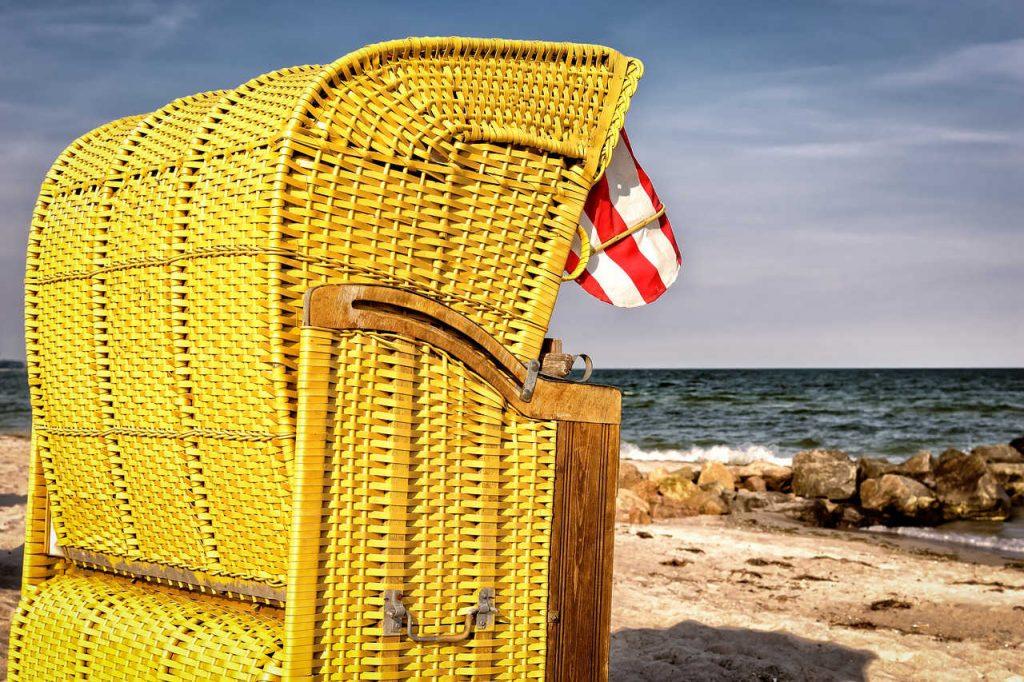 Gelber Strandkorb am Meer mit rot-weiß gestreifter Markise und bewegtem Meer. Illustration zum Beitrag Weste/Top aus Norogarn Taiyo Sport 6 von Noromaniac. Foto: Pixabay