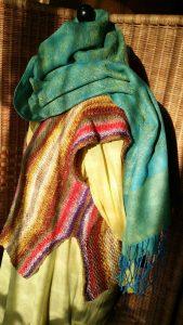 Die Weste (das Top) aus dem Garn Noro Taiyo Sport 6 von der Seite auf gelber Bluse mit türkisblauem Schal im Sonnenlicht, von Noromaniac. Foto: Katrin Walter
