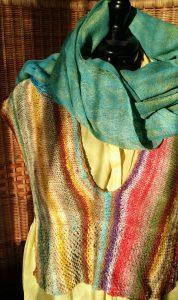 Das Top (die Weste) aus Norogarn Taiyo Sport 6 von vorn auf gelber Bluse mit türkisblauem Schal im Sonnenlicht, von Noromaniac. Foto: Katrin Walter