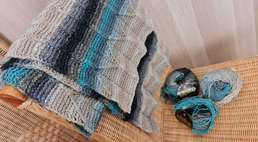 The Origami Shawl design here made from the yarn Noro Shiro color #2 in beige, gray, black and turquoise casually thrown over the back of the chair, also looks good so as home accessories. Photo: Katrin Walter - Noromaniac