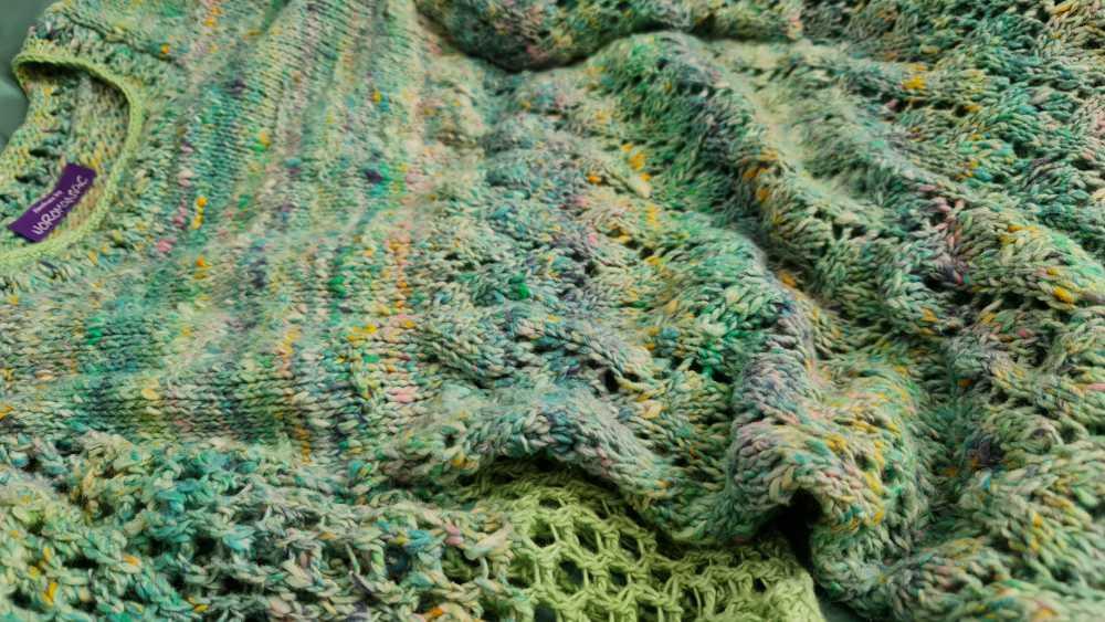 Liegend der Pulli aus Noro Kakigori #13 Fukuyama und Noro Sonata # #26 Jade. Wie Wasser scheinen die Muster zu fließen und machen dem Namen des Pullis alle Ehre: Laguna. Foto und Design: Katrin Walter – Noromaniac