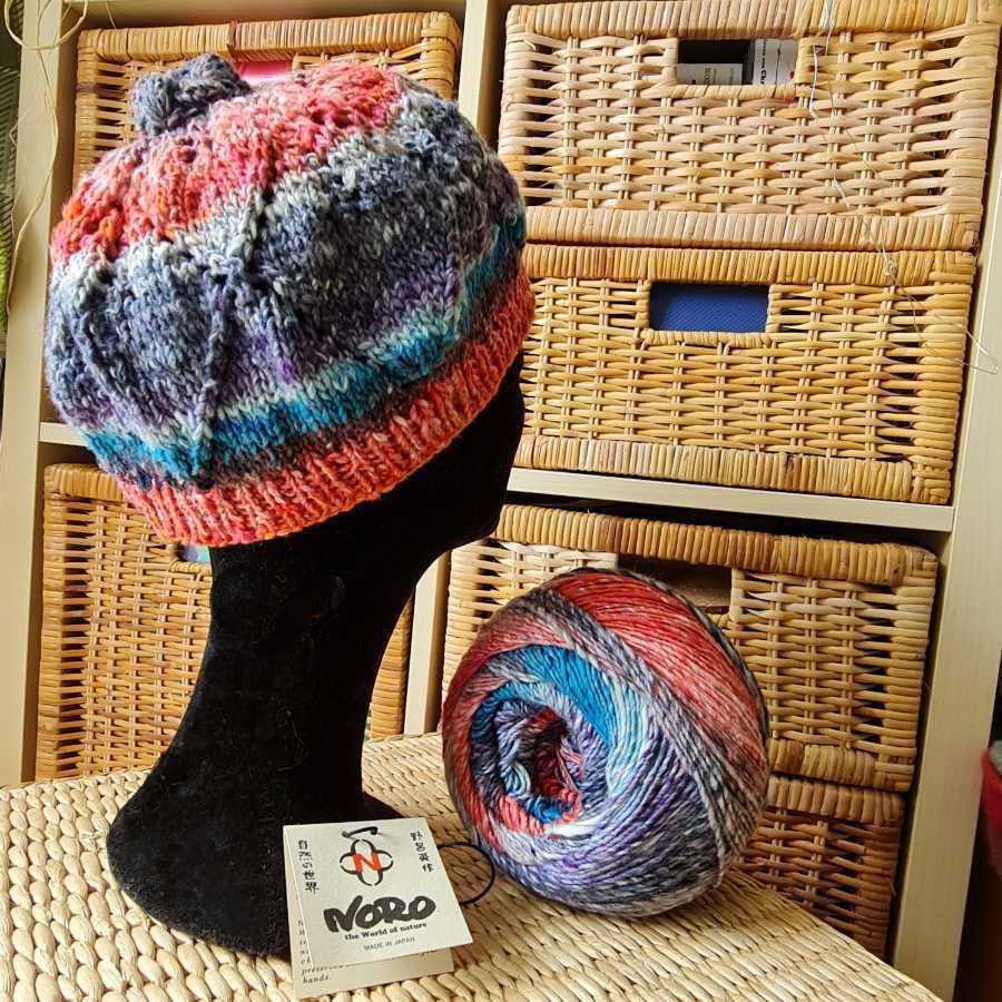Der Roxy Hat von Noromaniac im Lace-Muster aus Norogarn Farbe #5 Fukuoka auf einem Perückenständer. Foto: Katrin Walter
