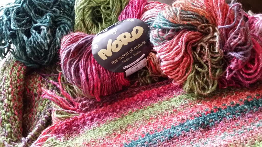 Im Vordergrund der Schal mit seinen Ausgangsmaterialien: Noro Silk Garden 265, Noro Silk Garden Solo 33 und 48. Foto: Katrin Walter, Noromaniac