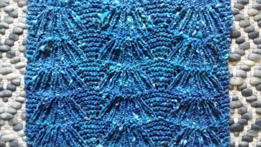 Türkisblau wie das Meer schillern die gestrickten Muscheln auf diesem breiten gestrickten Schal aus Norowolle. Foto: Katrin Walter - Noromaniac