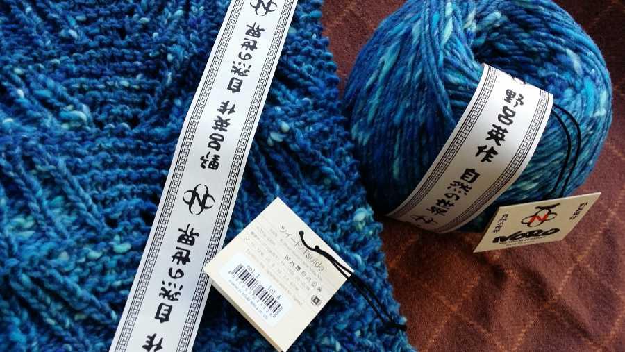 Die Wolle Noro Tsuido #1, einmal im Knäuel, einmal gestrickt mit Noroschild und Band. Foto: Katrin Walter – Noromaniac