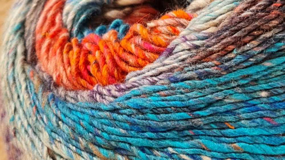 Nahaufnahme des Garns Noro Enka #05 Fukuoka mit Orange-Pink, Coelinblau, Violettblau+etwas Purpur+Weiß - ein Feuerwerk an Farben. Foto: Katrin Walter – Noromaniac