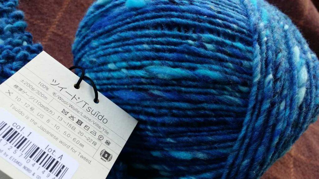 Noro Tsuido #1 als Garnknäuel in Türkis-Blau mit Schild, auf dem die Qualität beschrieben ist. Foto: Katrin Walter - Noromaniac