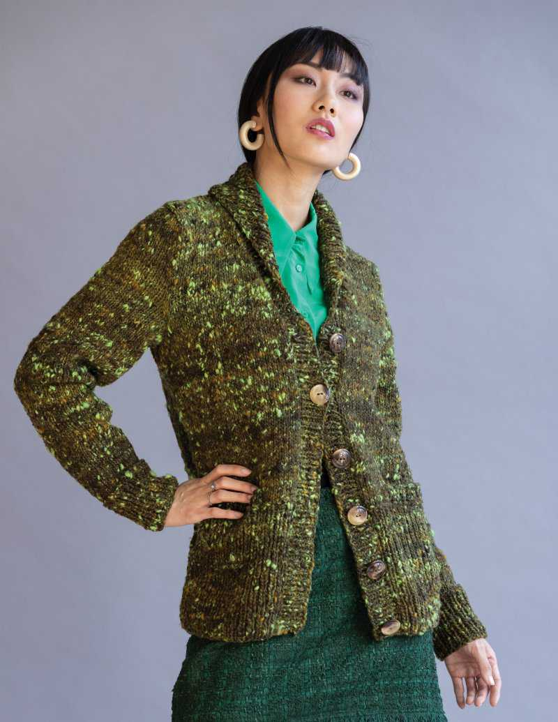 Die Schalkragenjacke in Grün aus der Noro Tsuido #8 hier gestylt mit grünem Rock und Bluse - Foto: Noro Knitting Magazine - Noromaniac